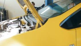 El mecánico levanta el coche amarillo en el servicio del automóvil del garaje - pequeña empresa metrajes