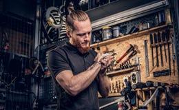 El mecánico limpia sus brazos después del manual.N-POS=30 de reparaciones de la bici Fotografía de archivo libre de regalías