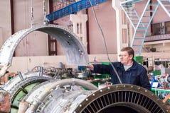 El mecánico mayor monta el motor de la aviación Imágenes de archivo libres de regalías