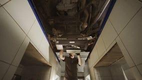El mecánico mueve y prepara el soporte del servicio para la alineación de rueda, estación del coche, reparación de la suspensión, almacen de video