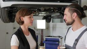 El mecánico principal del retrato y el cliente femenino, hablan de trabajo bien almacen de metraje de vídeo