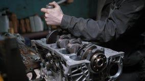 El mecánico repara el bloque de motor en un garaje metrajes