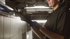 El mecánico se coloca en el hoyo del coche y lleva a guantero antes de reparar, estación del coche, reparación de la suspensión,  almacen de video