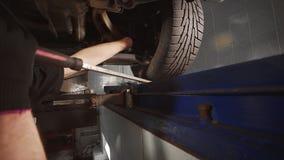 El mecánico se coloca en el hoyo y la suspensión en la gasolinera del coche, reparación de la suspensión, hoyo del vehículo, rued almacen de metraje de vídeo