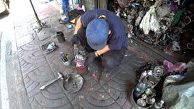 El mecánico trabaja en una acera en capital tailandesa metrajes