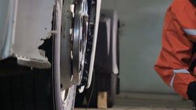 El mecánico utiliza el destornillador neumático para desatornillar el neumático de la rueda almacen de metraje de vídeo