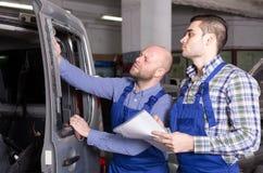 El mecánico y el agente de seguro examinan el coche Imagenes de archivo