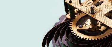 El mecanismo antiguo del reloj del mecánico en fondo azul, los dientes de bronce rueda la visión macra Profundidad del campo baja Fotografía de archivo libre de regalías