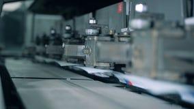 El mecanismo de la fábrica con las cubiertas de papel se está moviendo lentamente almacen de video