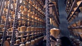 El mecanismo de la fábrica es de elevación y de baja de filas de los conos de la oblea con helado almacen de video