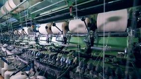 El mecanismo de la fábrica está enrollando los carretes blancos Materia textil, equipo que hace punto en una fábrica de la produc almacen de video