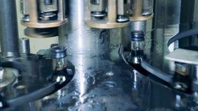 El mecanismo moderno pone los casquillos en las botellas con alcohol Producción de whisky, escocesa, coñac metrajes