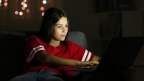 El mecanografiar adolescente en un ordenador portátil en la noche en casa metrajes