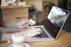 El mecanografiar con la tarjeta de crédito en café Imagen de archivo libre de regalías