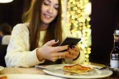 El mecanografiar de la mujer escribe el mensaje en el teléfono elegante en un café moderno Imagen cosechada de la muchacha bonita Imagenes de archivo