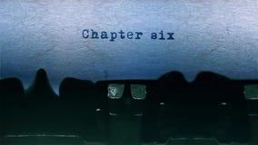 El mecanografiar de la palabra del capítulo seis se centró en una hoja de papel en viejo audio de la máquina de escribir