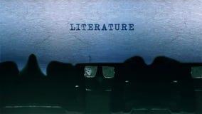 El mecanografiar de la palabra de la literatura se centró en una hoja de papel en viejo audio de la máquina de escribir