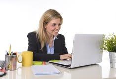 El mecanografiar de trabajo rubio caucásico feliz joven de la mujer de negocios del retrato corporativo en el ordenador portátil Imagen de archivo libre de regalías