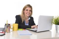 El mecanografiar de trabajo rubio caucásico feliz joven de la mujer de negocios del retrato corporativo en el ordenador portátil Foto de archivo libre de regalías