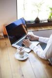 El mecanografiar en el ordenador en café Fotos de archivo