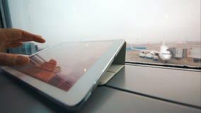 El mecanografiar en la tableta en alféizar en el aeropuerto almacen de video