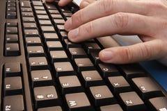 El mecanografiar en un teclado Foto de archivo