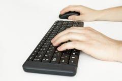 El mecanografiar en un teclado y el mouseing Fotografía de archivo libre de regalías