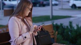 El mecanografiar joven y mensajería de la mujer en el teléfono al aire libre, inclinando el tiro metrajes