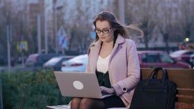 El mecanografiar stydent de la mujer en el ordenador portátil que se sienta en banco en parque de la ciudad metrajes