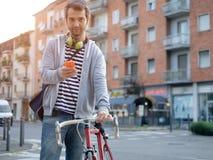 El mecanografiar vestido casual adulto joven en el teléfono en la calle de la ciudad Imagen de archivo