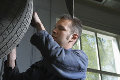 El mecánico Changing un coche rueda adentro el garaje Imagen de archivo