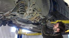 El mecánico experto que quita el coche llevado parte en garaje debajo del automóvil almacen de video