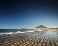 El medano beach and montana roja landscape in tenerife spain. El medano tourist beach and montana roja famous coast landscape in tenerife spain Stock Images