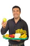 El mediados de hombre adulto feliz elige la manzana verde Imagenes de archivo
