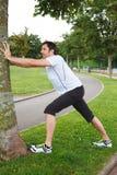 El mediados de hombre adulto que hace estirar ejercita usando un árbol Foto de archivo