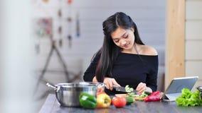 El medio tiró el pepino asiático joven bastante sonriente del corte de la mujer que se sentaba en la tabla en cocina almacen de metraje de vídeo