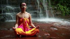 El meditar con la pintura facial en cascada de la selva tropical de Borneo almacen de metraje de vídeo