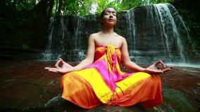 El meditar con la pintura facial en cascada de la selva tropical de Borneo almacen de video