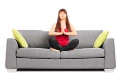 El meditar de la chica joven asentado en un sofá Foto de archivo libre de regalías
