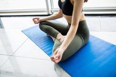 El meditar de la muchacha de la yoga interior y fabricación de un símbolo del zen con su mano Primer del cuerpo de la mujer en ac Foto de archivo libre de regalías