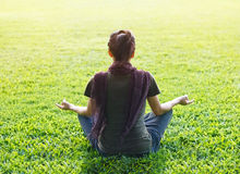 El meditar de la mujer de la yoga al aire libre en parque en fondo del campo de hierba Imágenes de archivo libres de regalías
