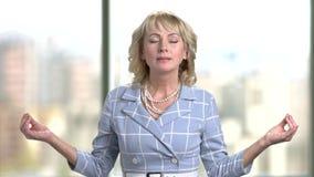 El meditar de la mujer de negocios maduros interior en oficina almacen de metraje de vídeo