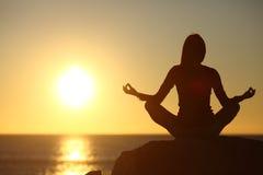 El meditar de la mujer y yoga practicante que miran el sol Fotografía de archivo