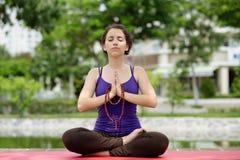 El meditar en la posición de la yoga del loto Foto de archivo