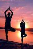 El meditar en la salida del sol junto Foto de archivo libre de regalías