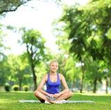 El meditar femenino joven en un parque Fotos de archivo libres de regalías