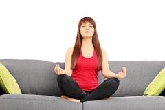 El meditar joven de la hembra asentado en un sofá Fotos de archivo libres de regalías