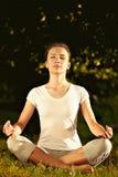 El meditar modelo femenino en armonía serena en la posición de loto en parque Foto de archivo libre de regalías