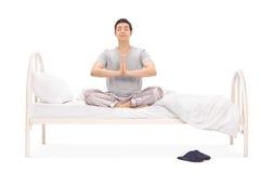 El meditar tranquilo del hombre joven asentado en una cama Imagen de archivo