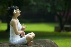 El Meditating asiático hermoso de la mujer al aire libre Fotos de archivo libres de regalías
